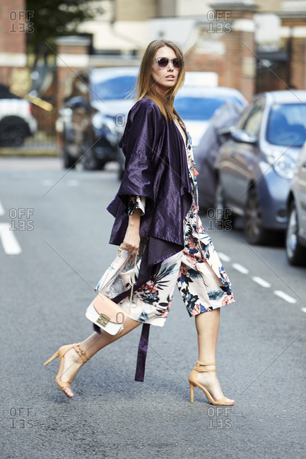 LONDON - 19 SEPTEMBER, 2017: Woman wearing sunglasses, floral print shorts and high heels crossing the road, Day 5, London Fashion Week.