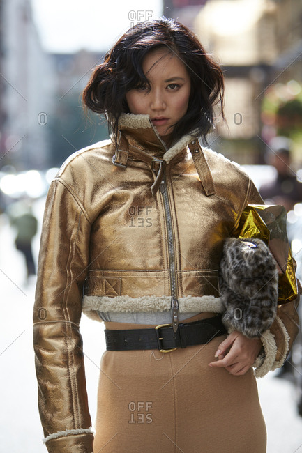 LONDON - 19 SEPTEMBER, 2017: Fashion designer Betty Bach wearing short gold flying jacket, carrying leopard fake fur clutch bag, Day 5, London Fashion Week.