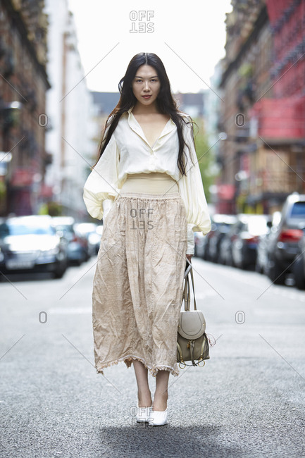 LONDON - 19 SEPTEMBER, 2017: Woman wearing white bell-sleeved blouse and long beige skirt standing in the road, Day 5, London Fashion Week.