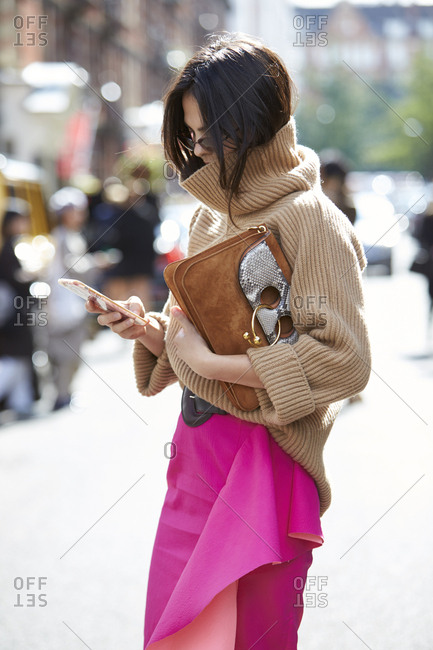 LONDON - 19 SEPTEMBER, 2017: Fashion blogger and model Doina Ciobanu standing in street wearing a pink skirt, beige Paul Smith sweater, using smartphone holding a JW Anderson handbag, Day 5, London Fashion Week.