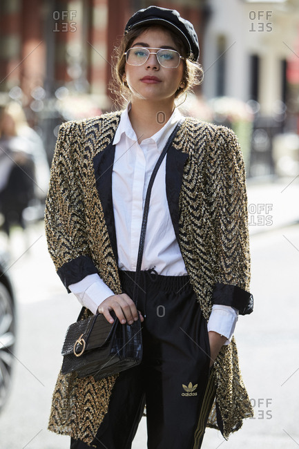 LONDON - 19 SEPTEMBER, 2017: Woman standing in the street wearing gold and black herringbone long jacket, black cap, white shirt and black Adidas track pants, Day 5, London Fashion Week.