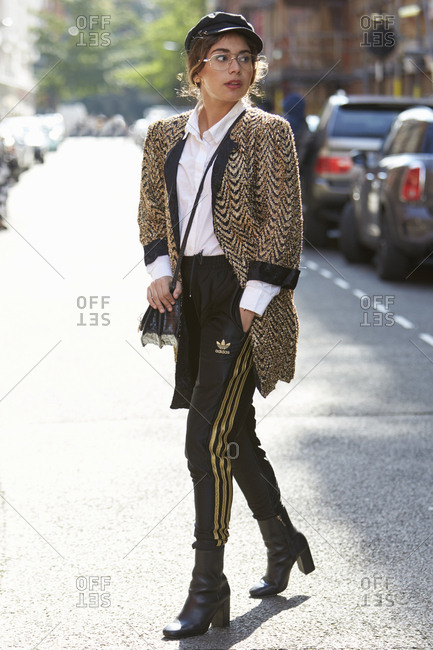 LONDON - 19 SEPTEMBER, 2017: Woman walking in the street wearing gold and black herringbone long jacket, black cap, white shirt, black Adidas track pants and ankle boots, Day 5, London Fashion Week.