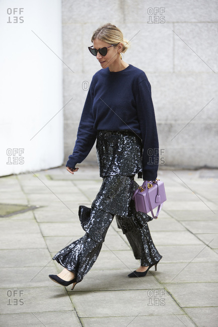 LONDON - 19 SEPTEMBER, 2017: Fashion stylist, blogger and editor of the Icons, Laura Fantacci walking in the street wearing black sequined flared trousers carrying a Mark Cross lilac Grace box bag, Day 5, London Fashion Week.