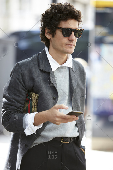 LONDON - 19 SEPTEMBER, 2017: Alvaro de Juan, fashion and beauty editor of Esquire magazine Spain, suing smartphone on the street, Day 5, London Fashion Week.