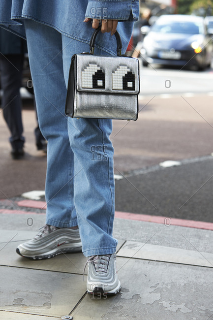 LONDON - 18 SEPTEMBER, 2017: Low section of guest at LFW standing in street wearing jeans, oversized denim shirt and sports shoes, holding a handbag decorated with pixelated eyes design, Day 4, London Fashion Week.