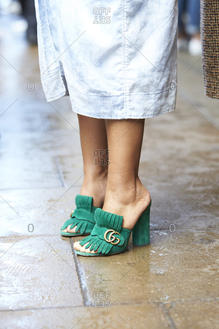 LONDON - 18 SEPTEMBER, 2017: Low section of guest at LFW standing in the street wearing green suede Gucci heels with a long skirt, Day 4, London Fashion Week.
