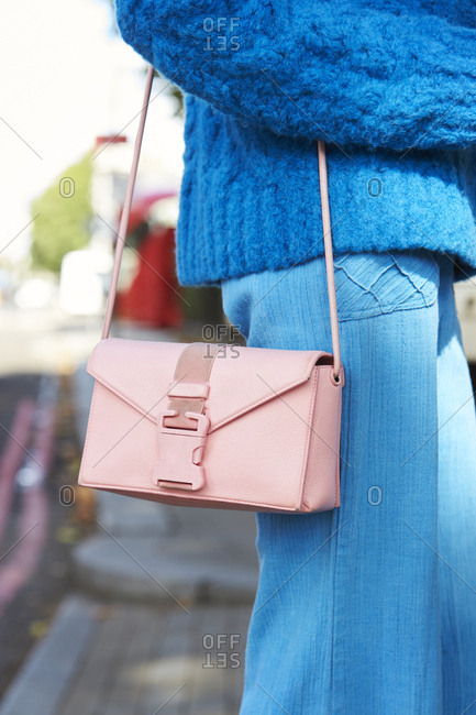 LONDON - 18 SEPTEMBER, 2017: Mid section detail of woman standing on the street wearing blue knitted sweater with blue trousers and pink Christopher Kane handbag, Day 4, London Fashion Week.