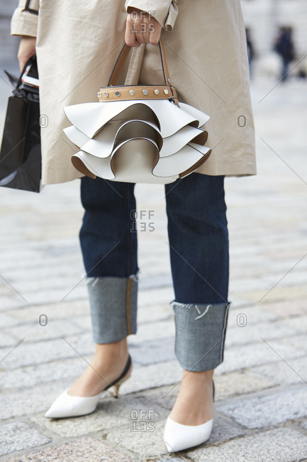 LONDON - 18 SEPTEMBER, 2017: Low section of woman standing in the street wearing a beige mac and jeans with turn ups holding a Zara frilled bucket handbag, Day 4, London Fashion Week.