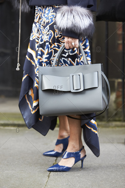 LONDON - 19 SEPTEMBER, 2017: Low section of guest at LFW wearing patterned silk scarf skirt and fur cuffed jacket and blue Nicholas Kirkwood shoes, holding grey Boyy handbag, Day 5, London Fashion Week.