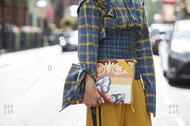 LONDON - 19 SEPTEMBER, 2017: Mid section of guest at LFW standing in the street holding Balenciaga clutch bag, Day 5, London Fashion Week.