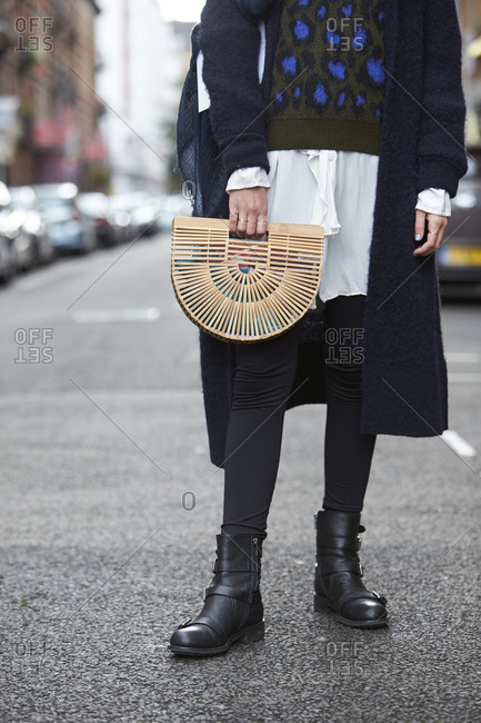 LONDON - 19 SEPTEMBER, 2017: Low section of guest at LFW wearing black coat, blue patterned top over white blouse, black leggings and ankle boots, holding a Cult Gaia Ark bamboo handbag, Day 5, London Fashion Week.