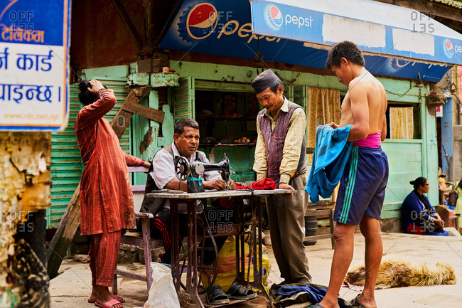 Thamel District, Kathmandu, Nepal - July 30, 2017: Customers watching a local tailor work