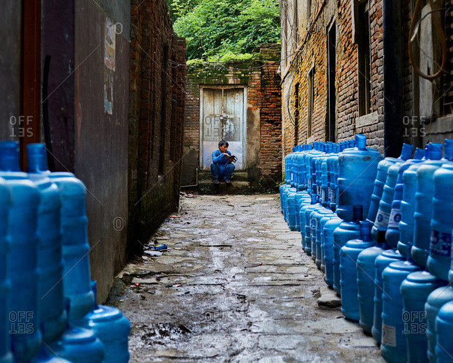 Thamel District, Kathmandu, Nepal - July 30, 2017: Man sitting in an alleyway with empty water bottles