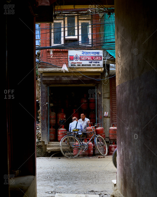Thamel District, Kathmandu, Nepal - July 30, 2017: Men talking in front of a bottled gas store