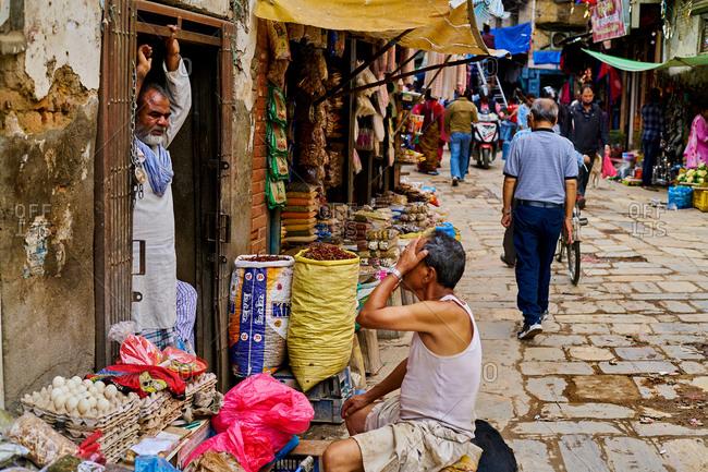 Thamel District, Kathmandu, Nepal - July 30, 2017: Shop keepers talking on a busy street