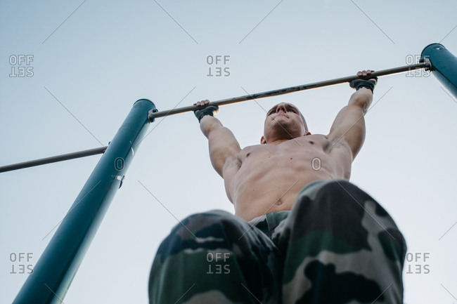 Young muscular man training in park