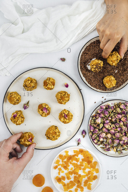 A man and a woman making pumpkin balls photographed from top view. Diced apricot, flax seeds and rose petals accompany.