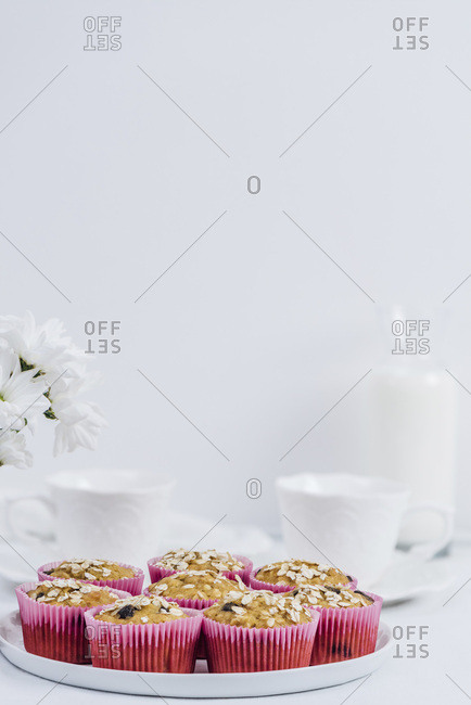 Pumpkin oatmeal muffins served on a white plate photographed on a white background. White flowers, white cups and a bottle of milk accompany.