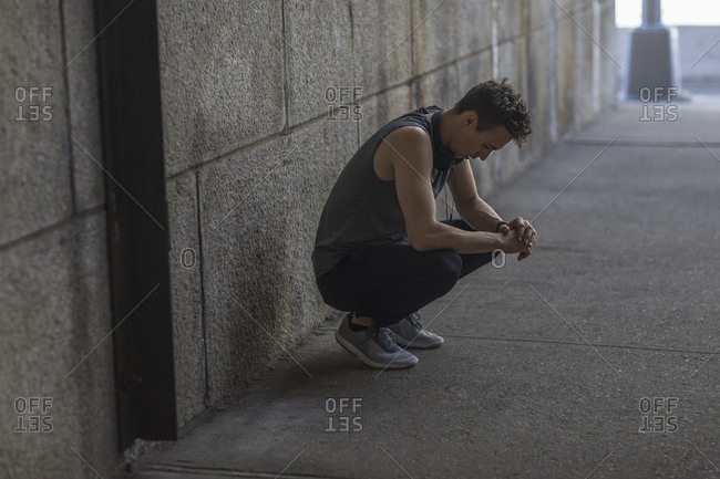 Tired young man crouching after exercising on road