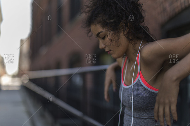 Tired female jogger in sportswear resting after exercise