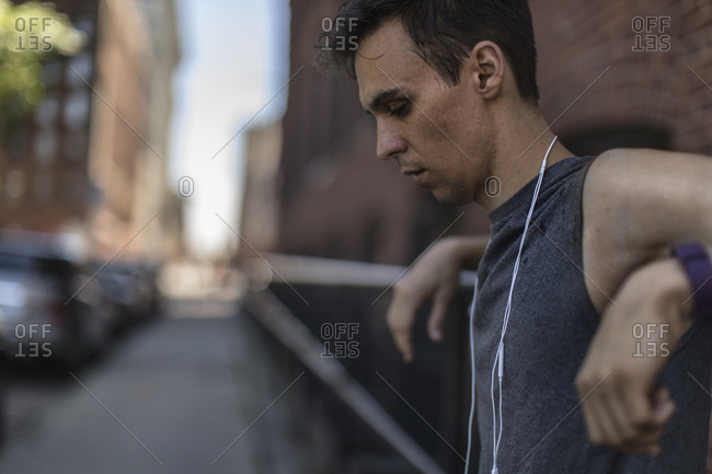 Tired male jogger in sportswear leaning on railing in city
