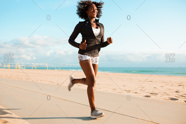 Full length of happy young woman jogging on footpath at beach