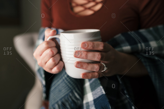Person with a blanket draped over their arms holding a white mug