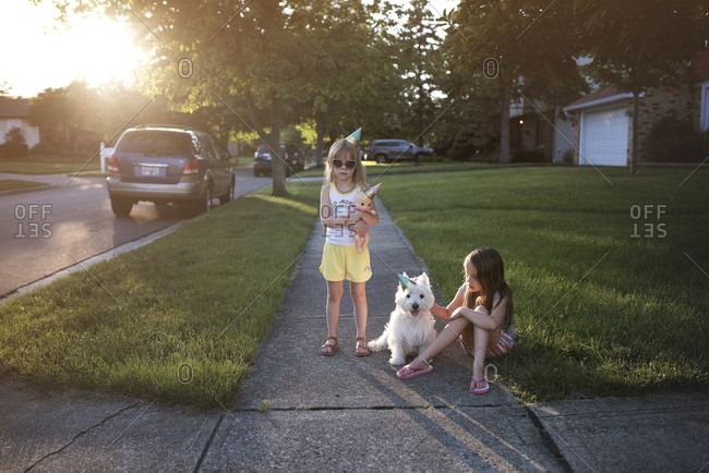 Girl holding doll standing on sidewalk and girl sitting on lawn petting her dog wearing a party hat