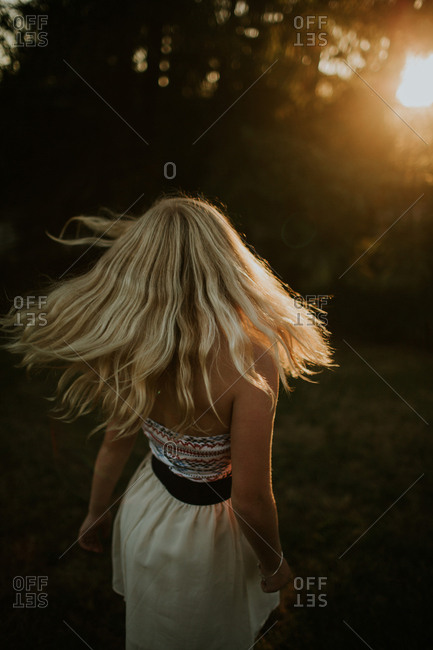 Woman twirling her blonde hair outdoors