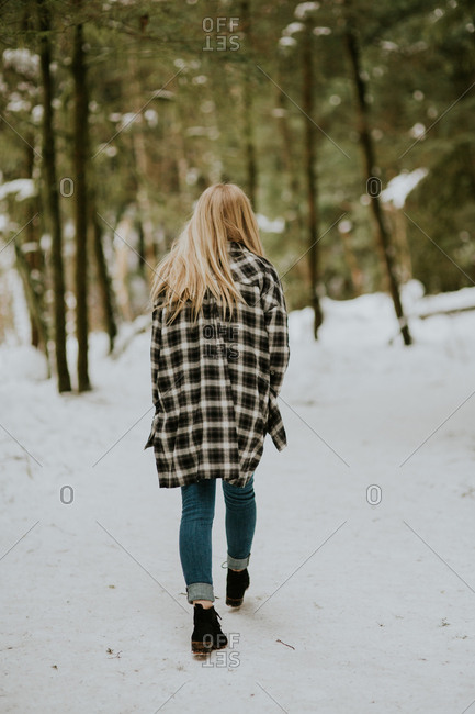 Young woman walking away on snow covered path in the forest