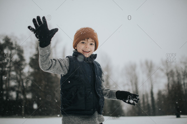 Boy waving while playing outside on a snowy day