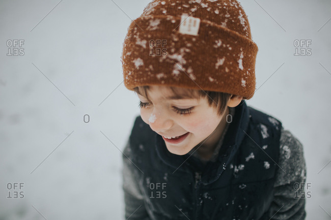Smiling boy with snowflakes landing on his face