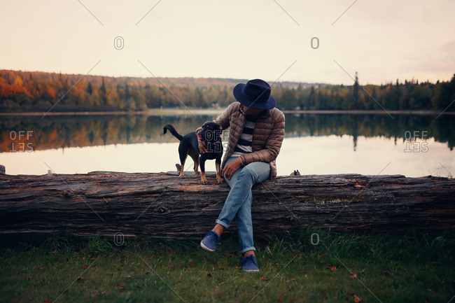 Man and puppy sitting on a log by a lake