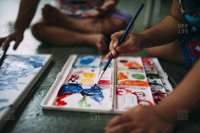 Two young children mixing watercolor paints
