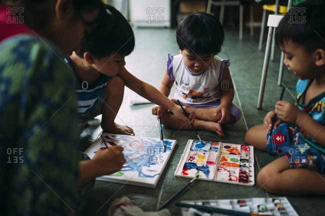 Three young kids creating a watercolor painting with an adult