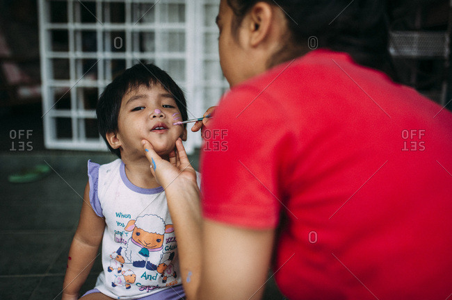 Woman painting a child's face with face paint