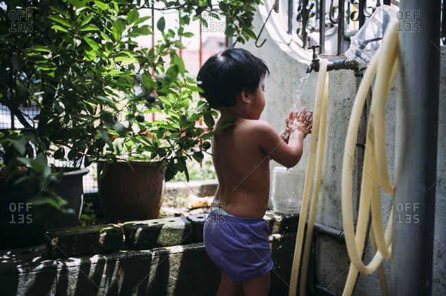 Young child washing hands in water faucet outside