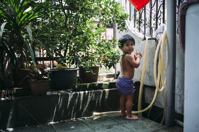 Young child using water faucet outside
