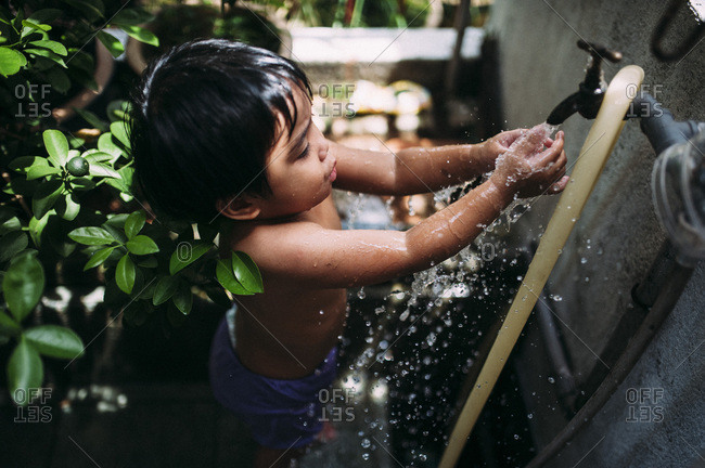 Young child washing hands in the garden