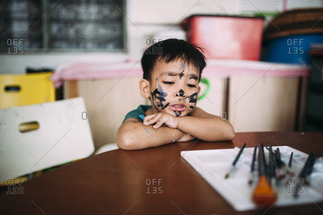 Toddler in face paint sitting at a table