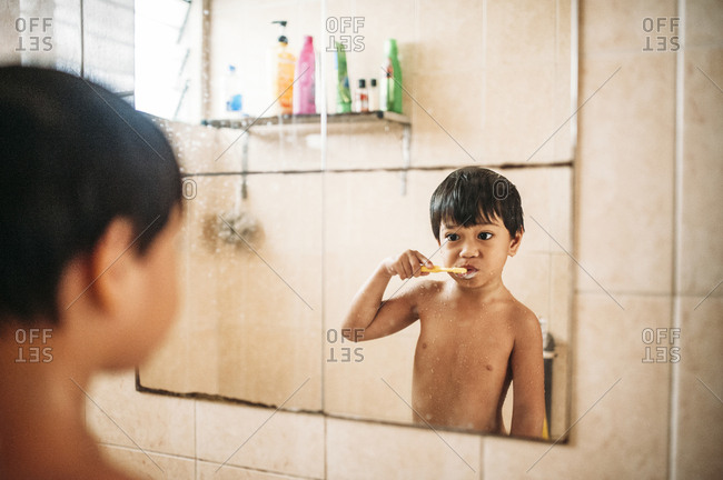 Boy brushing his teeth in the mirror