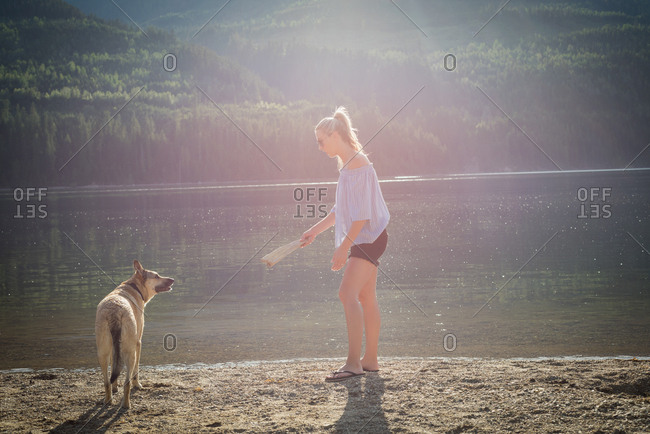 Woman playing with dog near river on a sunny day