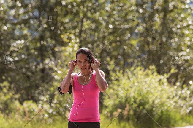 Fit woman listening to music on headphones in forest on a sunny day