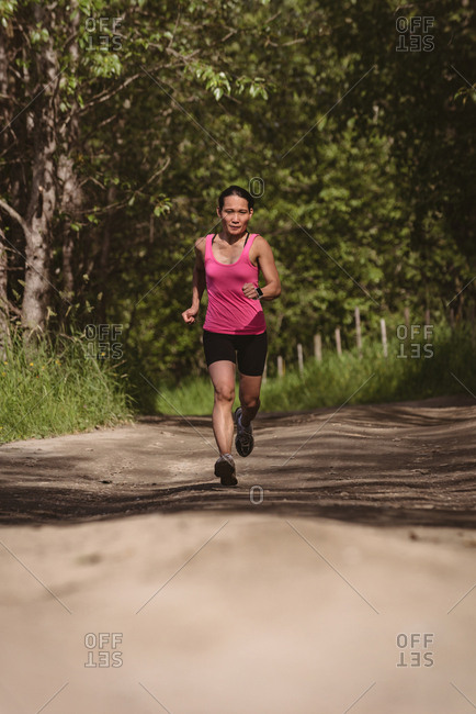 Fit woman jogging in forest road on a sunny day