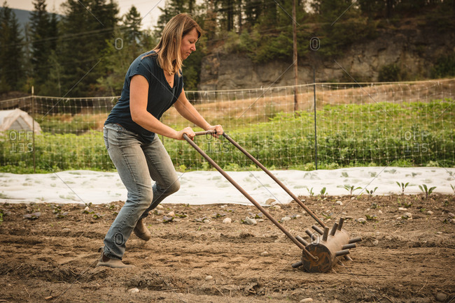 Female farmer ploughing a field with agriculture equipment in farm