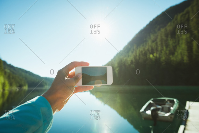 Man taking picture with mobile phone on a sunny day