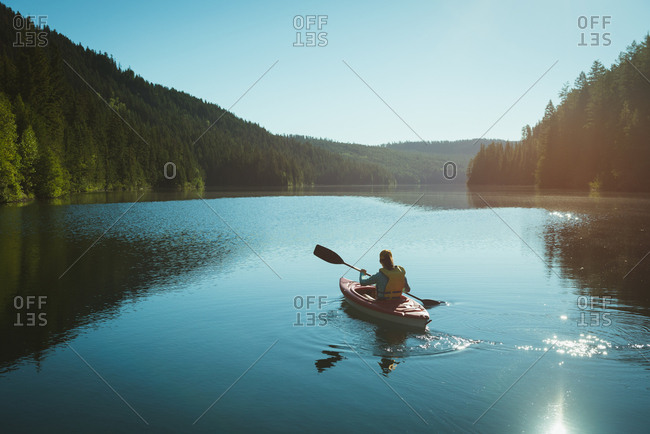 Man kayaking in river on a sunny day