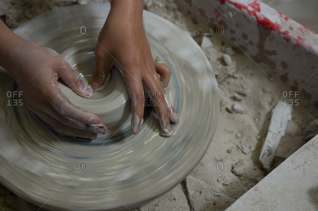 Hands of girl molding a clay in pottery workshop