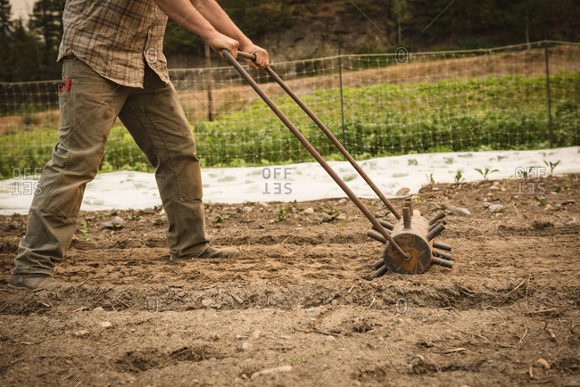 Farmer ploughing a field with agriculture equipment in farm
