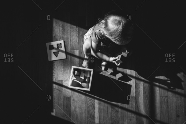 Toddler playing in window light